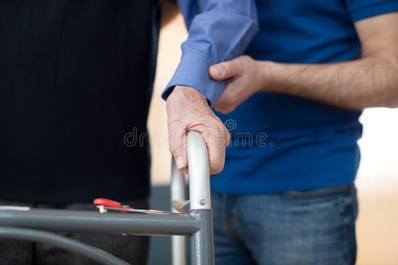 Ο πρεσβύτερος επανδρώνει τα χέρια στον περπατώντας εργαζόμενο πλαισίων με προσοχή σε Backgrou στοκ φωτογραφία
