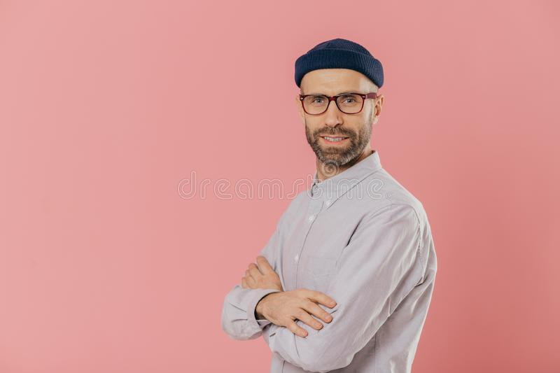 Ο πυροβολισμός στούντιο του μόνου σίγουρου γενειοφόρου ατόμου με τα μπλε μάτια, φορά το μοντέρνο καπέλο και το άσπρο πουκάμισο, κ στοκ εικόνα με δικαίωμα ελεύθερης χρήσης