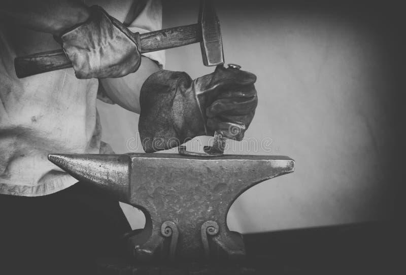 Ο πυροβολισμός λεπτομέρειας του εργασίας του μετάλλου σε έναν σιδηρουργό σφυρηλατεί στοκ εικόνα