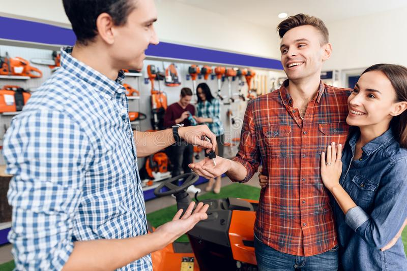 Ο πωλητής δίνει τα κλειδιά στο νέο τύπο και στο κορίτσι στοκ φωτογραφίες