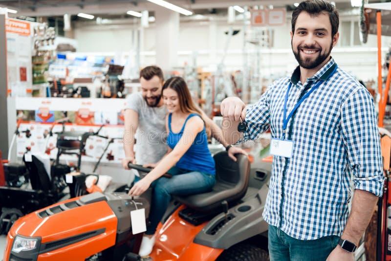 Ο πωλητής θέτει με το ζεύγος των πελατών και των κλειδιών για τον καθαρισμό της μηχανής στο κατάστημα εργαλείων δύναμης στοκ εικόνες με δικαίωμα ελεύθερης χρήσης