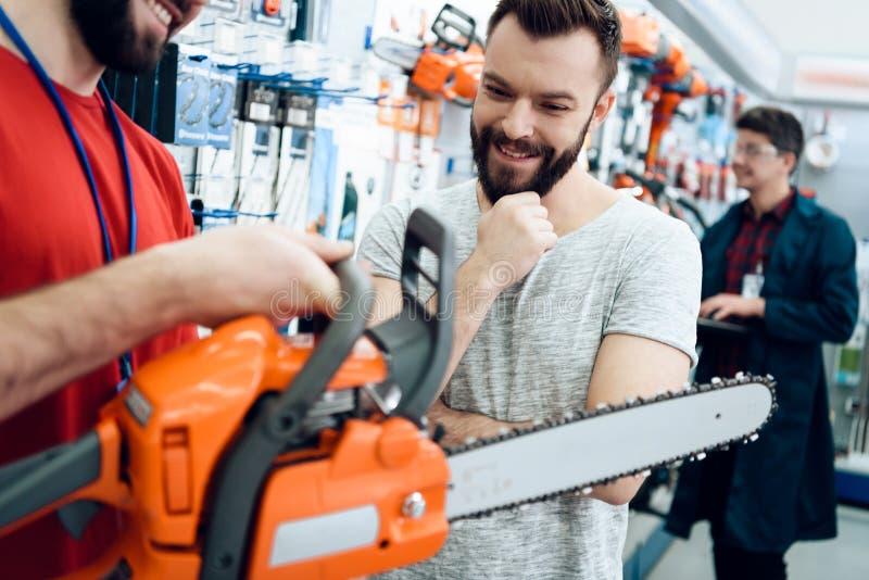 Ο πωλητής παρουσιάζει γενειοφόρο νέο αλυσιδοπρίονο πελατών στο κατάστημα εργαλείων δύναμης στοκ φωτογραφίες