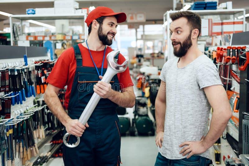 Ο πωλητής παρουσιάζει γενειοφόρο νέο γιγαντιαίο γαλλικό κλειδί πελατών στο κατάστημα εργαλείων δύναμης στοκ εικόνα με δικαίωμα ελεύθερης χρήσης