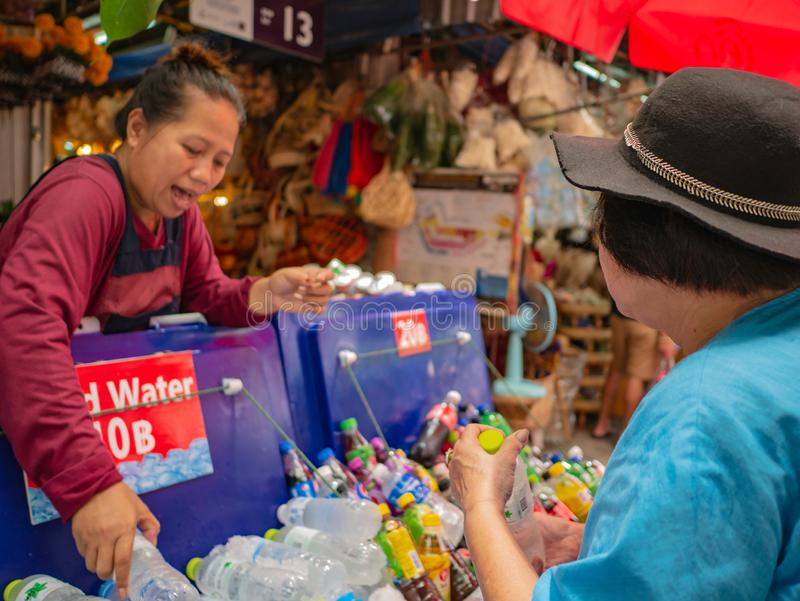 : ο πωλητής που πωλεί το νερό του μπουκαλιού στον τουρίστα στην αγορά Μπανγκόκ Ταϊλάνδη Σαββατοκύριακου Chatuchak στοκ φωτογραφίες
