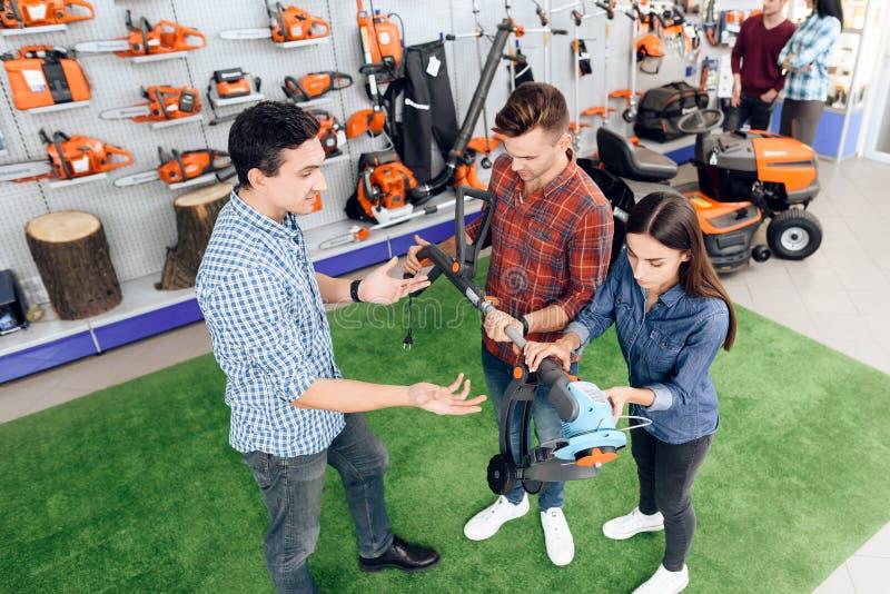 Ο πωλητής στο κατάστημα παρουσιάζει στους πελάτες κόπτη χλόης στοκ φωτογραφίες