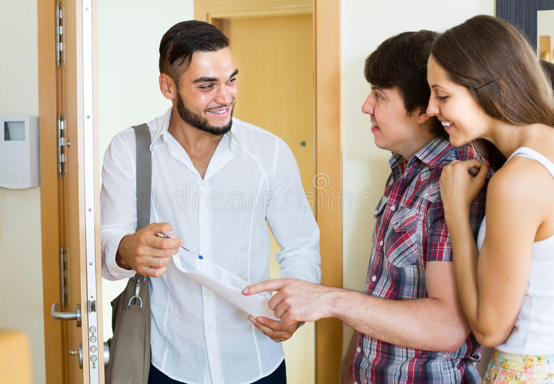 Ο πωλητής παρουσιάζει το πρόγραμμά του που στέκεται κοντά στην πόρτα εισόδων στοκ εικόνα με δικαίωμα ελεύθερης χρήσης