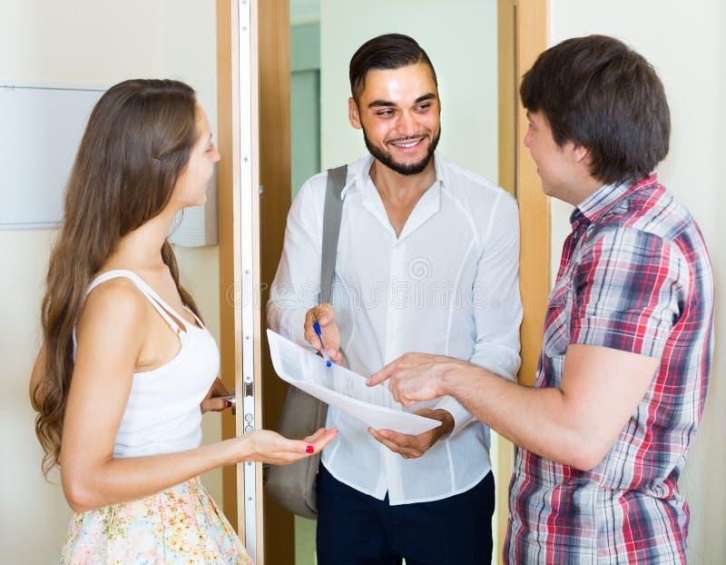 Ο πωλητής παρουσιάζει το πρόγραμμά του που στέκεται κοντά στην πόρτα εισόδων στοκ εικόνα