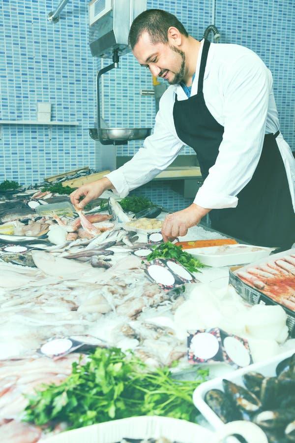 Ο πωλητής στη μαύρη ποδιά παρουσιάζει ψάρια αντίθετα στοκ εικόνα