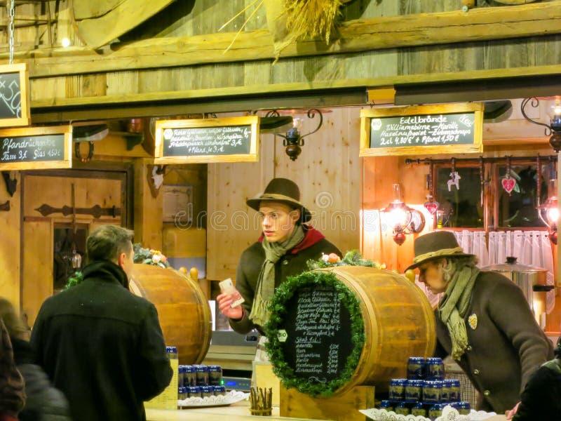 Ο πωλητής χύνει το καυτό θερμαμένο κρασί στην αγορά Χριστουγέννων