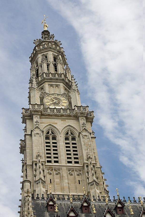 Ο πύργος καμπαναριών του γοτθικού Δημαρχείου στη γαλλική πόλη Arras σε έναν μπλε ουρανό με το άσπρο υπόβαθρο σύννεφων, παγκόσμια  στοκ εικόνα
