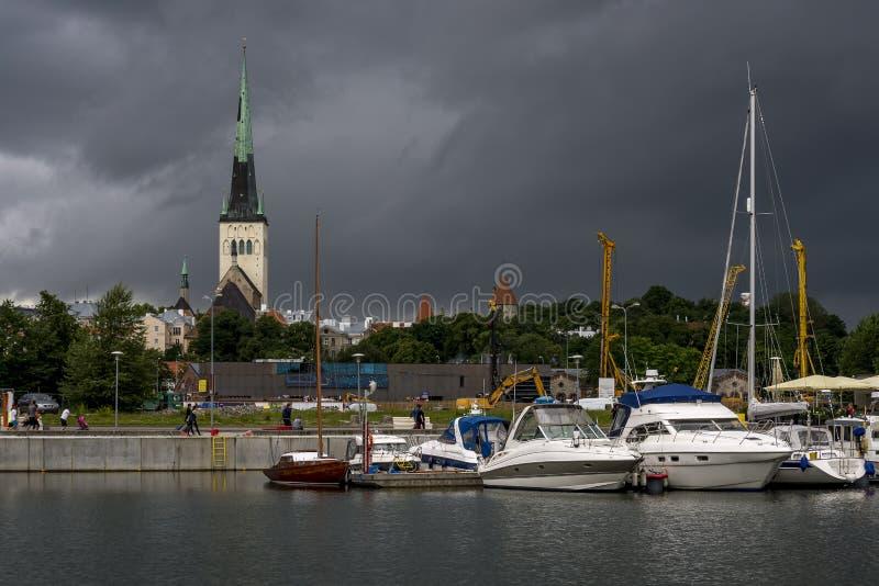Ο πύργος κουδουνιών της εκκλησίας του ST Olav και του κέντρου του Ταλίν, Εσθονία, που βλέπει από το λιμένα με έναν θυελλώδη ουραν στοκ φωτογραφίες