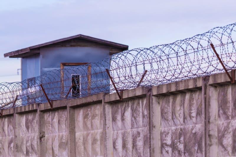 Ο πύργος φύλαξης και ο φράκτης με τον οδοντωτό - καλώδιο της φυλακής στοκ εικόνα