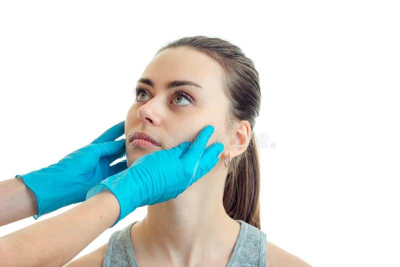 Ο πλαστικός χειρούργος στα μπλε γάντια κρατά μια κινηματογράφηση σε πρώτο πλάνο νέων κοριτσιών προσώπων στοκ φωτογραφία με δικαίωμα ελεύθερης χρήσης