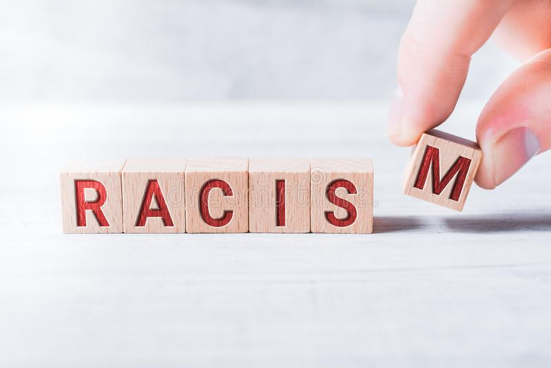 Ο ρατσισμός του Word που διαμορφώνεται από τους ξύλινους φραγμούς και που τακτοποιείται από τα αρσενικά δάχτυλα σε έναν άσπρο πίν στοκ φωτογραφία με δικαίωμα ελεύθερης χρήσης