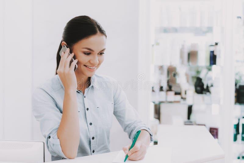 Ο ρεσεψιονίστ γυναικών μιλά τηλεφωνικώς στο σαλόνι ομορφιάς στοκ εικόνα