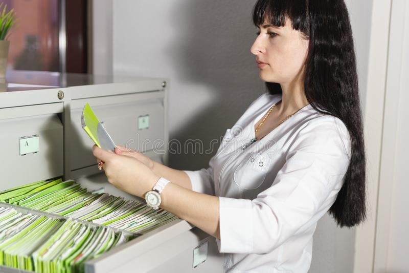 Ο ρεσεψιονίστ της ιατρικής κλινικής βρήκε στο συρτάρι του ραφιού και διαβάζει την επιθυμητή υπομονετική κάρτα στοκ φωτογραφία