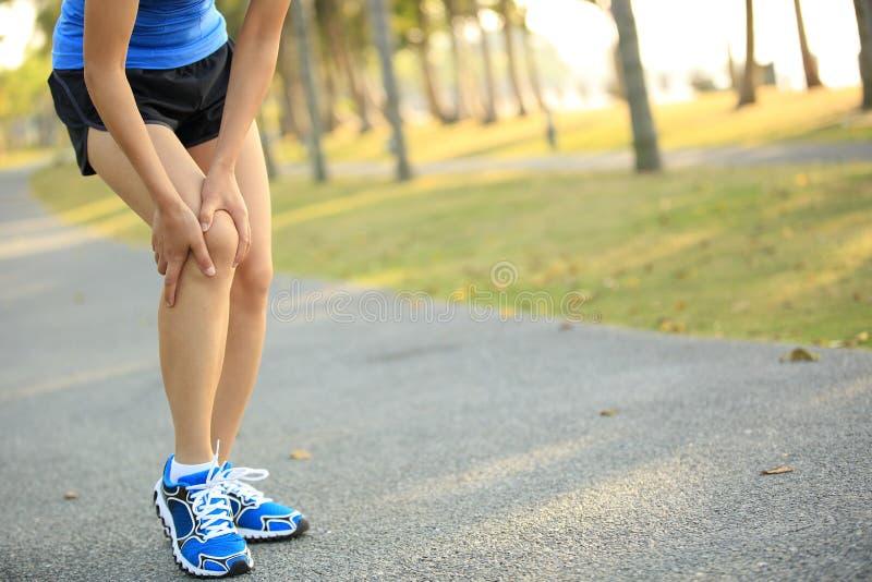 Ο δρομέας γυναικών κρατά τραυματισμένο το αθλητισμός γόνατό της στοκ εικόνα με δικαίωμα ελεύθερης χρήσης