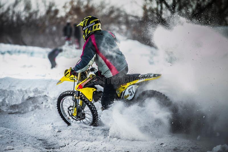 Ο δρομέας σε μια μοτοσικλέτα οδηγά με τη σειρά των ροδών έναν ψεκασμό του χιονιού και της λάσπης στοκ φωτογραφία
