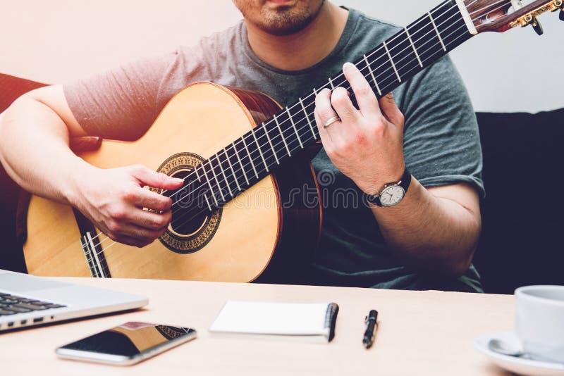 Ο ρομαντικός κιθαρίστας Συνθέτης ή παντρεμένος άνδρας παίζει κιθάρα που κάθεται σε μαύρο καναπέ στο σπίτι στοκ εικόνα