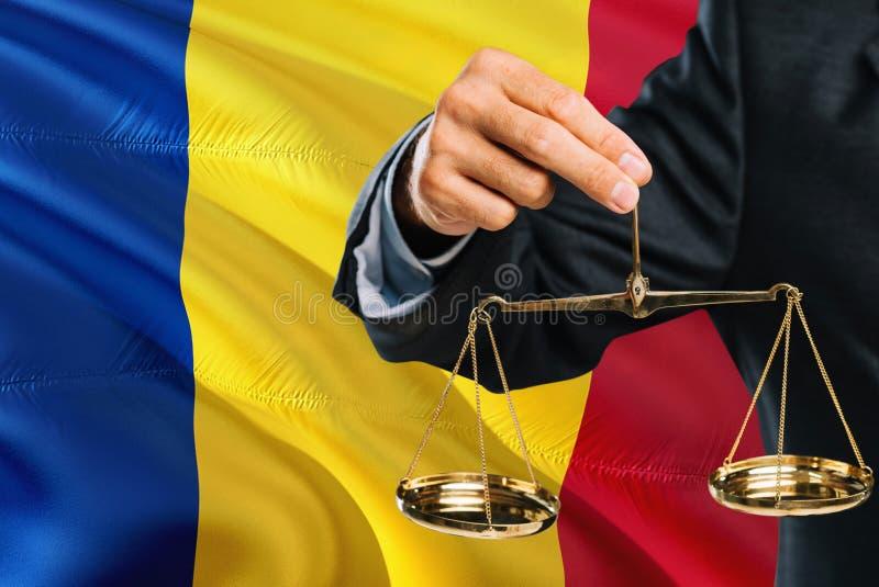 Ο ρουμανικός δικαστής κρατά τις χρυσές κλίμακες της δικαιοσύνης με το κυματίζοντας υπόβαθρο σημαιών της Ρουμανίας Θέμα ισότητας κ στοκ φωτογραφία