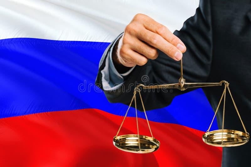 Ο ρωσικός δικαστής κρατά τις χρυσές κλίμακες της δικαιοσύνης με το κυματίζοντας υπόβαθρο σημαιών της Ρωσίας Θέμα ισότητας και νομ στοκ φωτογραφίες με δικαίωμα ελεύθερης χρήσης