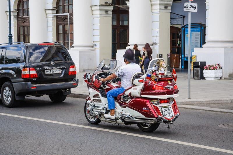 Ο ρωσικός οπαδός ποδοσφαίρου σε ένα χρυσό φτερό ` μοτοσικλετών ` Honda με το παιχνίδι Zabivaka στην πλάτη οδηγά στην οδό Varvarka στοκ εικόνες