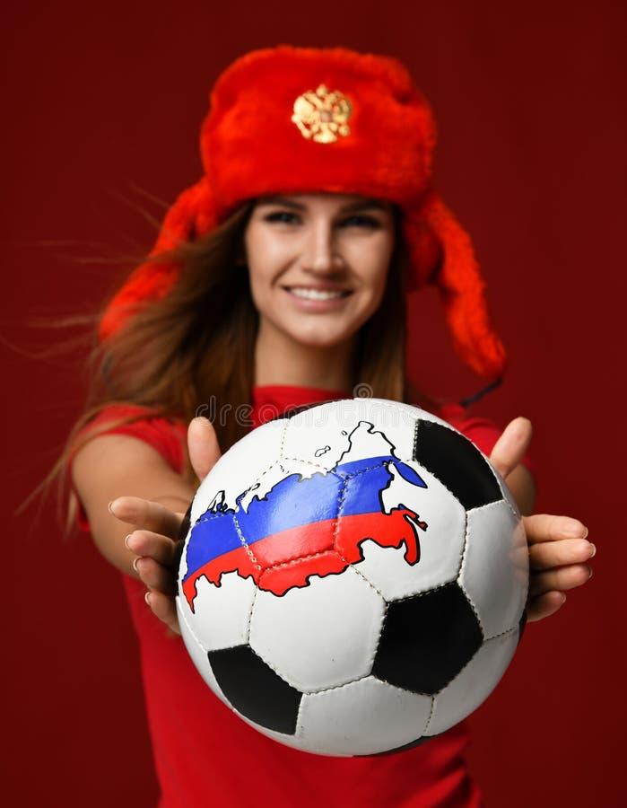Ο ρωσικός φορέας αθλητριών ανεμιστήρων ύφους κόκκινο σε ομοιόμορφο δίνει τη σφαίρα ποδοσφαίρου γιορτάζοντας το ευτυχές χαμόγελο στοκ εικόνες με δικαίωμα ελεύθερης χρήσης