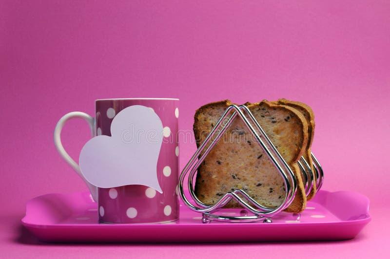 Ο ρόδινος δίσκος προγευμάτων με τη μορφή κουπών και καρδιών φλυτζανιών τσαγιού καφέ σημείων Πόλκα ψήνει το ράφι με τη wholemeal φρ στοκ εικόνες