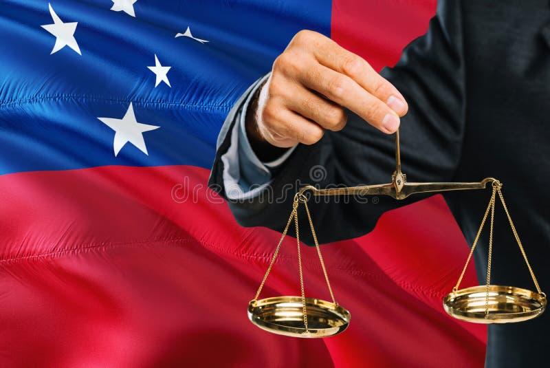 Ο σαμοανικός δικαστής κρατά τις χρυσές κλίμακες της δικαιοσύνης με το κυματίζοντας υπόβαθρο σημαιών της Σαμόα Θέμα ισότητας και ν στοκ φωτογραφία με δικαίωμα ελεύθερης χρήσης