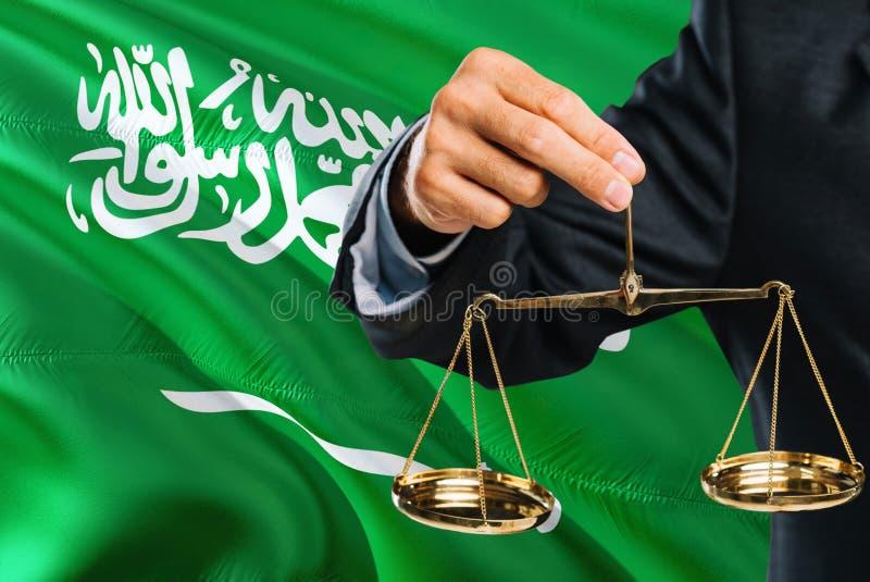Ο σαουδικός δικαστής κρατά τις χρυσές κλίμακες της δικαιοσύνης με το κυματίζοντας υπόβαθρο σημαιών της Σαουδικής Αραβίας Θέμα ισό στοκ εικόνα