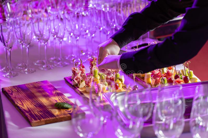 Ο σερβιτόρος προετοίμασε και εξυπηρετεί ένα πρόχειρο φαγητό Ο μπουφές στην υποδοχή Κατάταξη των καναπεδάκια στον ξύλινο πίνακα _ στοκ φωτογραφίες
