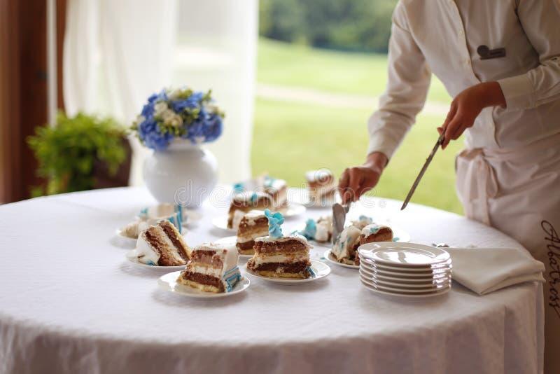 Ο σερβιτόρος φέρνει το γαμήλιο κέικ στοκ εικόνα