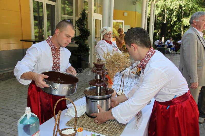 Ο σερβιτόρος δύο νεαρών άνδρων στα εθνικά ουκρανικά κοστούμια γέμισε την πηγή με την καυτή σοκολάτα για τα εθνικά πιάτα στοκ εικόνες