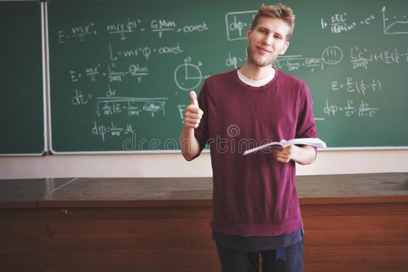 Ο σε απευθείας σύνδεση φυσικής αντίχειρας δασκάλων σειράς μαθημάτων νέος αρσενικός επάνω στην τάξη με τον πίνακα κιμωλίας με τους στοκ φωτογραφία με δικαίωμα ελεύθερης χρήσης