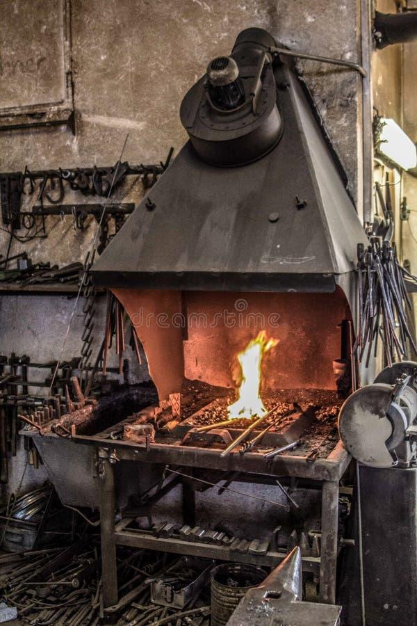 Ο σιδηρουργός σφυρηλατεί το φούρνο με το μέταλλο πυρκαγιάς στοκ φωτογραφίες με δικαίωμα ελεύθερης χρήσης