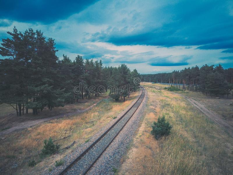 Ο σιδηρόδρομος πηγαίνει στην απόσταση που περιβάλλεται από τα πράσινα δέντρα μια νεφελώδη ημέρα στοκ εικόνα με δικαίωμα ελεύθερης χρήσης