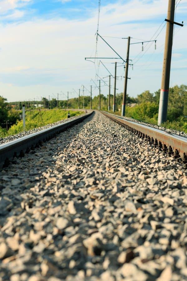 Ο σιδηρόδρομος, που περνά μέσω του δάσους, πηγαίνει στην απόσταση Μια σαφής, ηλιόλουστη θερινή ημέρα στοκ φωτογραφίες