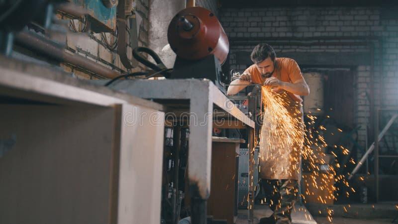 Ο σιδηρουργός σφυρηλατεί μέσα - ακονίζοντας εργαλεία σιδήρου με τα σπινθηρίσματα - το εργαστήριο μετάλλων στοκ εικόνες