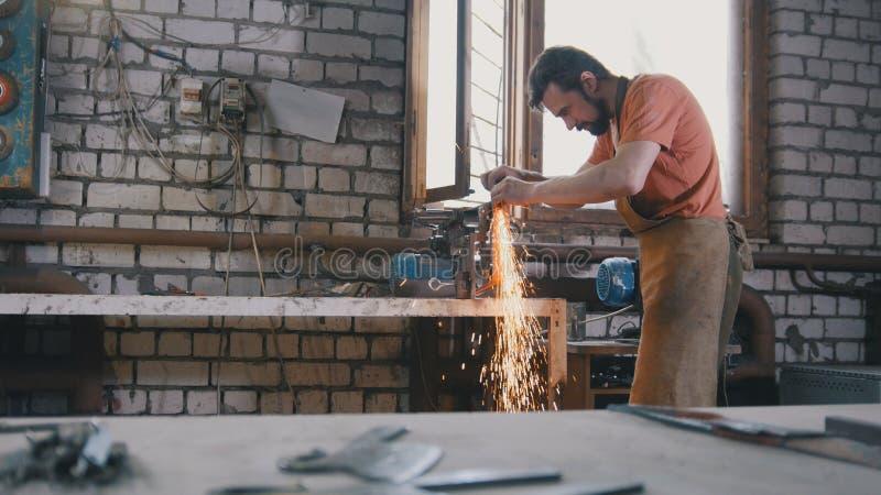 Ο σιδηρουργός σφυρηλατεί μέσα - ακονίζοντας εργαλεία σιδήρου με τα σπινθηρίσματα - το εργαστήριο μετάλλων στοκ εικόνα