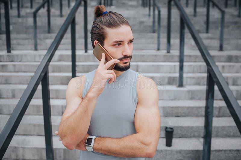 Ο σκοτεινός-μαλλιαρός και γενειοφόρος νεαρός άνδρας στέκεται και μιλά στο τηλέφωνο Κοιτάζει στο δικαίωμα Ο τύπος φορά handband Υπ στοκ εικόνα