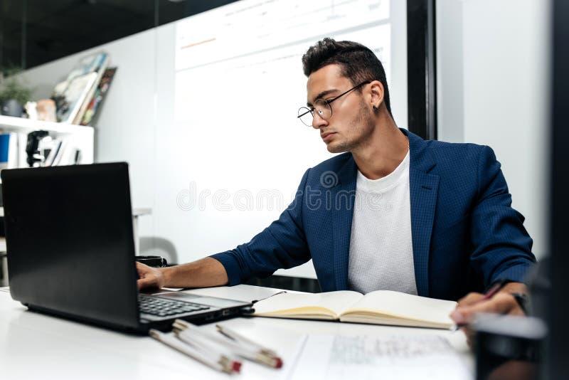 Ο σκοτεινός-μαλλιαρός νέος αρχιτέκτονας έντυσε σε μια εργασία μπλε ζακετών για το lap-top στο γραφείο στοκ φωτογραφίες