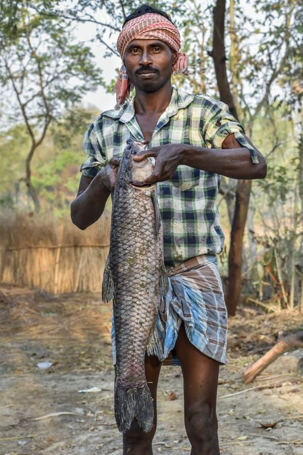 Ο σκοτεινός-ξεφλουδισμένος ινδικός ψαράς που κρατά ένα ψάρι Ctenopharyngodon Idella κυπρίνων χλόης από το χέρι του στοκ εικόνες με δικαίωμα ελεύθερης χρήσης
