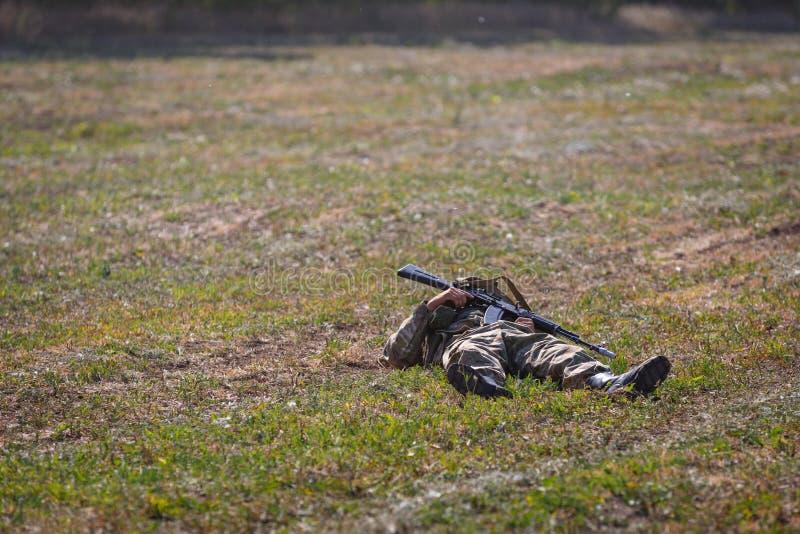 Ο σκοτωμένος στρατιώτης της ειδικής χρήσης αποσύνδεσης με ένα πυροβόλο όπλο στα χέρια του βρίσκεται στο πεδίο μάχη στοκ φωτογραφία με δικαίωμα ελεύθερης χρήσης