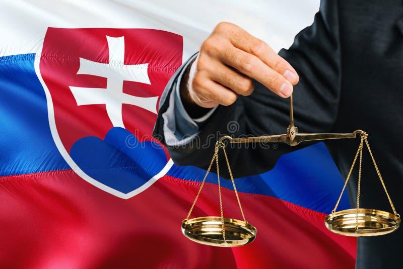 Ο σλοβάκικος δικαστής κρατά τις χρυσές κλίμακες της δικαιοσύνης με το κυματίζοντας υπόβαθρο σημαιών της Σλοβακίας Θέμα ισότητας κ στοκ φωτογραφία με δικαίωμα ελεύθερης χρήσης