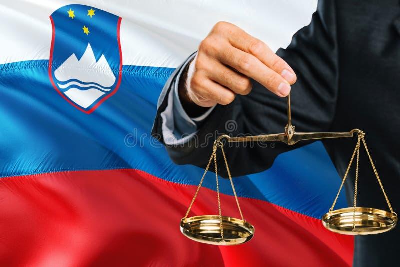 Ο σλοβένικος δικαστής κρατά τις χρυσές κλίμακες της δικαιοσύνης με το κυματίζοντας υπόβαθρο σημαιών της Σλοβενίας Θέμα ισότητας κ στοκ φωτογραφία με δικαίωμα ελεύθερης χρήσης