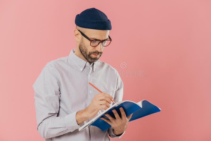 Ο σοβαρός αρσενικός συγγραφέας γράφει το δοκίμιο στο σημειωματάριο, αισθάνεται εμπνευσμένος, φορά τα γυαλιά και τα επίσημα ενδύμα στοκ φωτογραφία με δικαίωμα ελεύθερης χρήσης