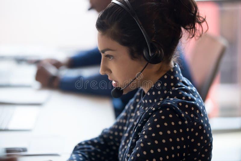Ο σοβαρός ινδικός θηλυκός πράκτορας στα ακουστικά συμβουλεύεται τον πελάτη στοκ εικόνες