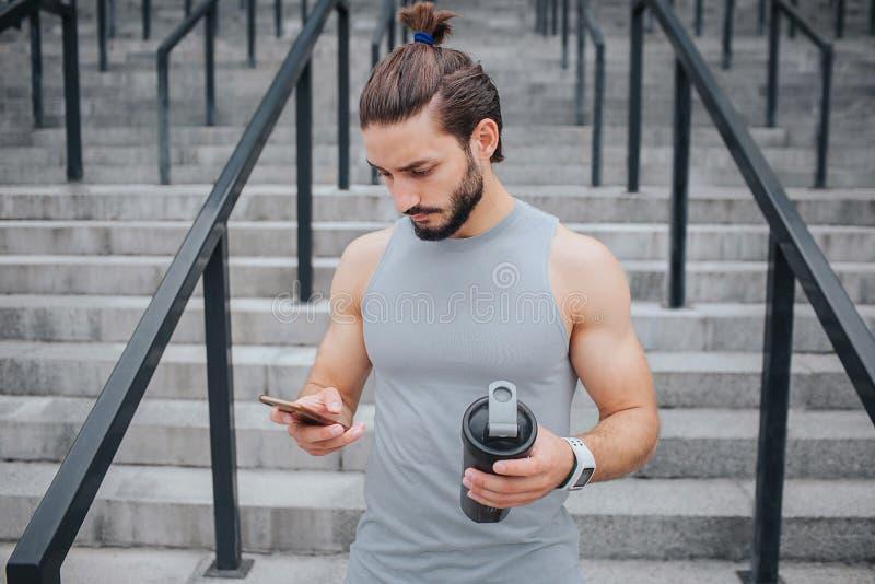 Ο σοβαρός και muscled νεαρός άνδρας στέκεται στα σκαλοπάτια και εξετάζει το τηλέφωνο αυτός HS σε ένα χέρι Υπάρχει μαύρο μπουκάλι  στοκ φωτογραφίες