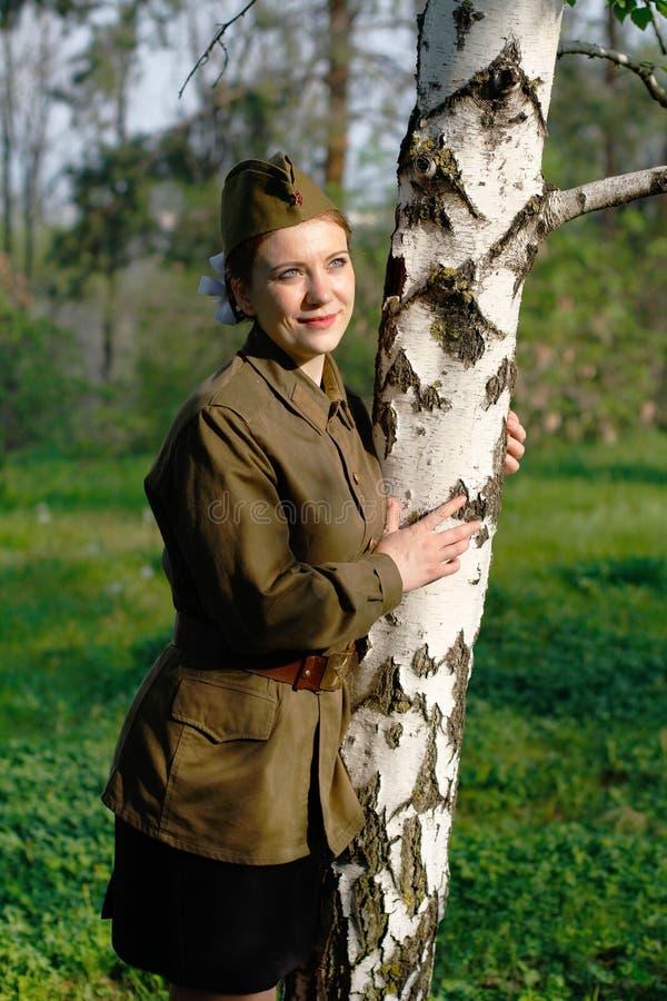 Ο σοβιετικός θηλυκός στρατιώτης σε ομοιόμορφο του Δεύτερου Παγκόσμιου Πολέμου στέκεται κοντά στη σημύδα στοκ εικόνα με δικαίωμα ελεύθερης χρήσης