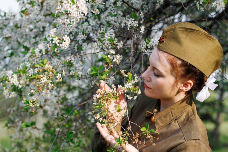 Ο σοβιετικός θηλυκός στρατιώτης σε ομοιόμορφο του Δεύτερου Παγκόσμιου Πολέμου στέκεται κοντά στο ανθίζοντας δέντρο στοκ φωτογραφία